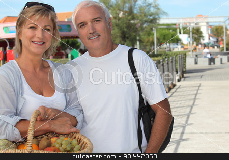 Couple on holiday with a basket of fruit stock photo, Couple on holiday with a basket of fruit by photography33