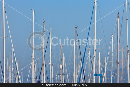 sailboat masts in a marina stock photo, sailboat masts in a marina against blue sky and distant hills by Marek Uliasz