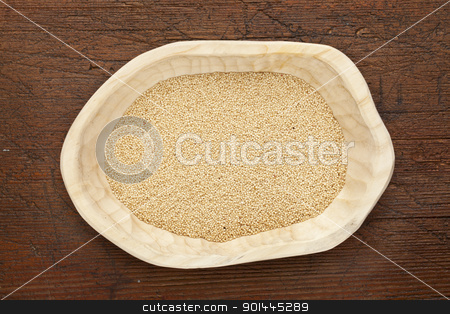 amaranth grain stock photo, amaranth igrain n a rustic wood bowl against grunge dark wooden table surface, top view by Marek Uliasz