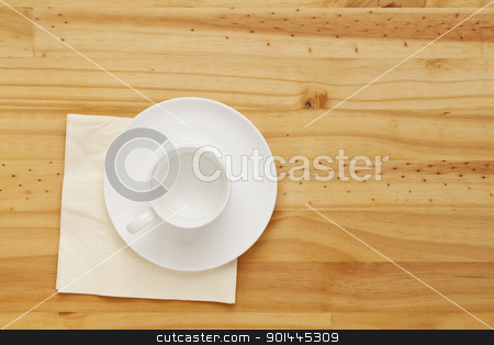empty coffee cup stock photo, empty white china coffee cup and napkin on pine wood table, top view by Marek Uliasz