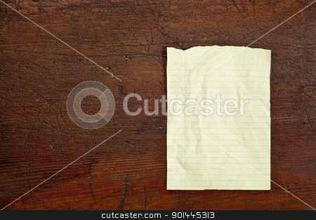 notepad paper sheet stock photo, yellow lined notepad paper sheet against dark grunge wood table by Marek Uliasz