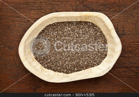 chia seeds in a rustic bowl stock photo, chia seeds (Salvia Hispanica) in a rustic wood bowl against grunge dark wooden table surface, top view by Marek Uliasz