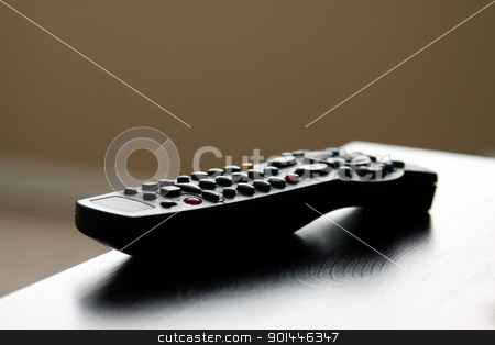 Remote Control on Table stock photo, A remote control sitting on table in a living room.  by Chris Hill
