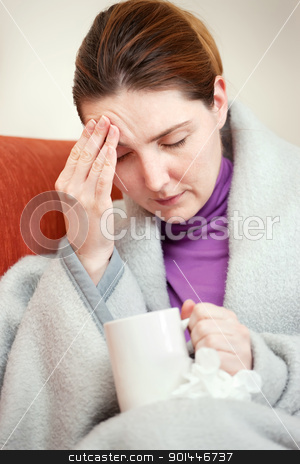 sick woman covered with blanket at home stock photo, A young sick woman covered with blanket at home by iMarin
