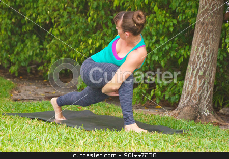 woman doing Yoga pose bound low lunge outdoors on grass stock photo, Young woman on yoga mat outdoors on the grass with trees in the  background in early morning light in bound low lunge posture. by Stephen Orsillo