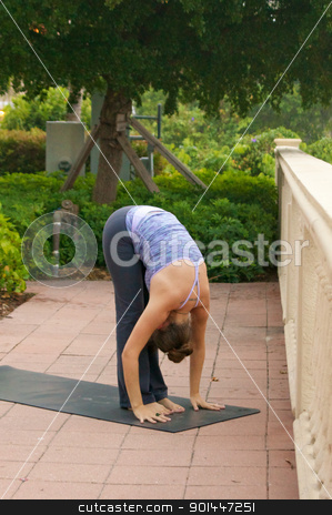 woman doing yoga posture forward fold outdoors in public on mat stock photo, an athletic brown haired woman is doing yoga exercise forward fold  pose outside on a sidewalk in public on an overcast morning. by Stephen Orsillo