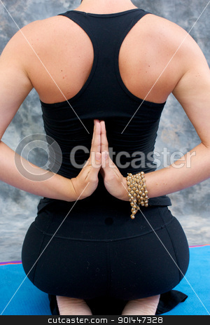 young woman in yoga Virasana  or hero pose with reverse prayer stock photo, young woman doing yoga exercise on mat in  Virasana or Hero Pose with reversed prayer or namaste in studio against a mottled background from behind. by Stephen Orsillo