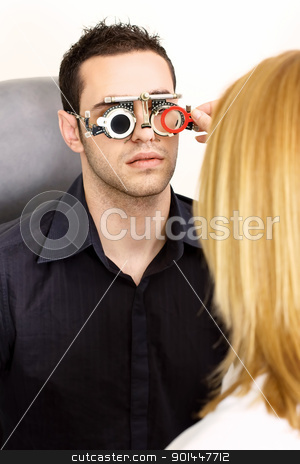 trial frame for eye testing stock photo, Male patient on medical attendance at the optometrist, wearing trial frame for eye testing by iMarin