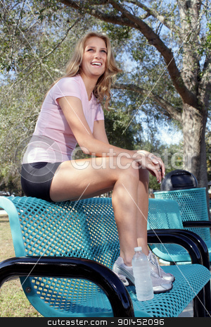 Beautiful Young Blonde Outdoors (9) stock photo, A lovely, young blonde with long, beautiful legs and wearing fitness wear, sits on a park bench outdoors. by Carl Stewart