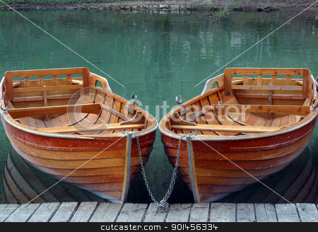 Rowboats parked in a row near a clear water lake stock photo, Rowboats parked in a row near a clear water lake by Zvonimir Atletic