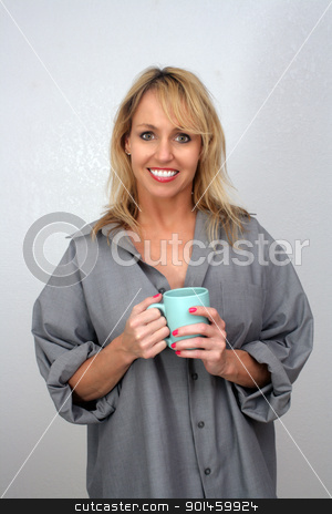 Beautiful Blonde Enjoying Hot Beverage (3) stock photo, A lovely blonde with a captivating smile and wearing a man's button-down shirt, enjoys a hot beverage. by Carl Stewart