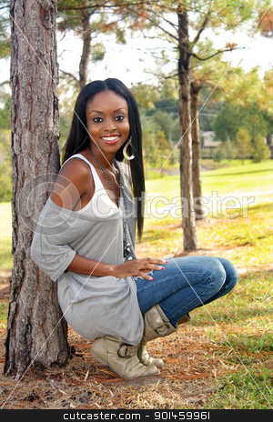 Beautiful Young Woman Outdoors (1) stock photo, An extraordinarily beautiful young woman with a bright, warm smile leans against a pine tree outdoors. by Carl Stewart