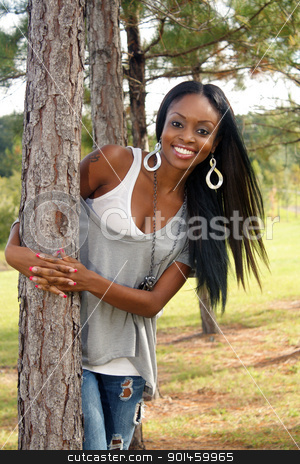 Beautiful Young Woman Outdoors (3) stock photo, An extraordinarily beautiful young woman with a bright, warm smile leans against a pine tree outdoors. by Carl Stewart