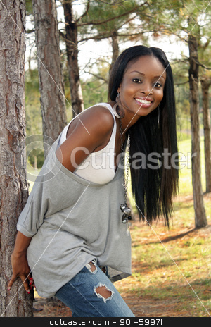Beautiful Young Woman Outdoors (5) stock photo, An extraordinarily beautiful young woman with a bright, warm smile leans against a pine tree outdoors. by Carl Stewart
