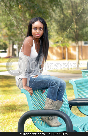 Beautiful Young Woman on a Park Bench (1) stock photo, An extraordinarily beautiful young woman sits on a park bench. by Carl Stewart