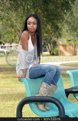 Beautiful Young Woman on a Park Bench (3) stock photo, An extraordinarily beautiful young woman sits on a park bench looking off-camera to frame left. by Carl Stewart