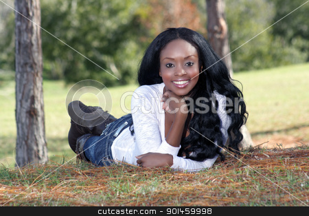 Beautiful Young Woman Lying in the Grass (2) stock photo, An extraordinarily beautiful young woman with a captivating smile, dressed in casual wear, lying in the grass outdoors. by Carl Stewart