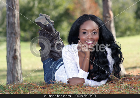 Beautiful Young Woman Lying in the Grass (3) stock photo, An extraordinarily beautiful young woman with a captivating smile, dressed in casual wear, lying in the grass outdoors. by Carl Stewart