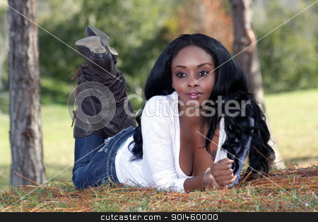 Beautiful Young Woman Lying in the Grass (4) stock photo, An extraordinarily beautiful and sophisticated young woman, dressed in casual wear, lying in the grass outdoors. by Carl Stewart