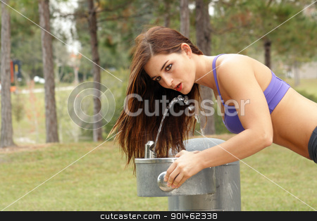 Beautiful Brunette Athlete at a Water Fountain (1) stock photo, A lovely young brunette athlete leans over to take a drink at an outdoor water fountain. by Carl Stewart
