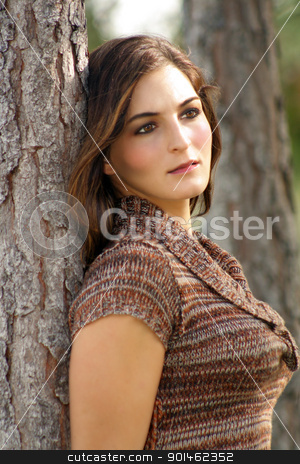 Lovely Young Brunette Outoors (2) stock photo, An attractive young brunette leans back against a pine tree. by Carl Stewart