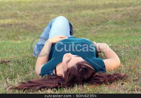 Lovely Young Brunette Outoors (4) stock photo, An attractive young brunette in casual wear relaxes outdoors, lying in the grass. by Carl Stewart