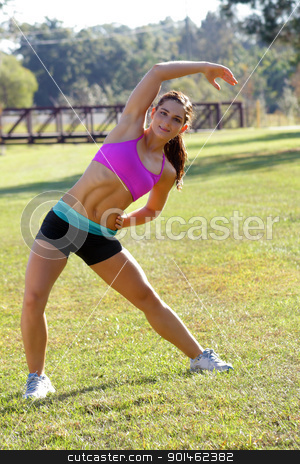 Beautiful Brunette Ahtlete Stretches Outdoors (3) stock photo, A lovely young brunette with remarkable abdominal musculature does stretching and warm-up outdoors. by Carl Stewart