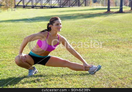 Beautiful Brunette Ahtlete Stretches Outdoors (5) stock photo, A lovely young brunette with remarkable abdominal musculature does stretching and warm-up outdoors. by Carl Stewart