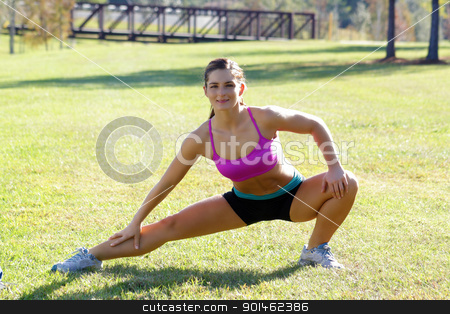 Beautiful Brunette Ahtlete Stretches Outdoors (7) stock photo, A lovely young brunette with remarkable abdominal musculature does stretching and warm-up outdoors. by Carl Stewart