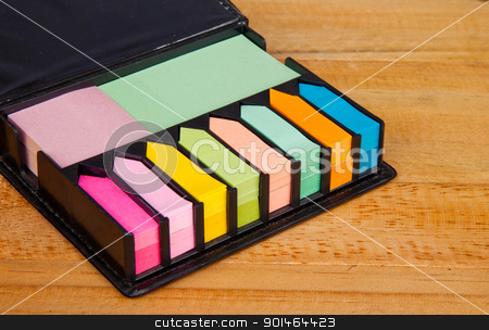 Multicolored post it note block in black leather case stock photo, Multicolored post it note block in black leather case on wood table by Yuttasak Jannarong