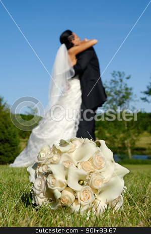 Wedding bouquet and couple stock photo, Wedding bouquet in focus and couple in the background holding each other. by Lars Christensen