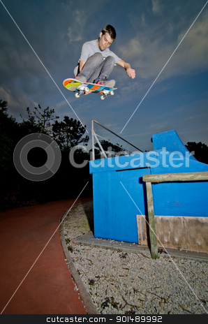 Skateboarder flying stock photo, Skateboarder flying over a fap on sunset at the local skatepark. by Homydesign 