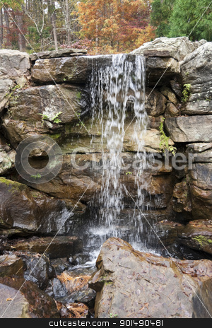 Waterfall stock photo, Water flowing over some rocks in the middle of a forest by Kevin Tietz