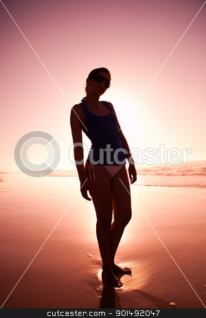 Woman silhouette on the beach stock photo, Female silhouette of a beautiful young girl on the beach at the sunset by ikostudio