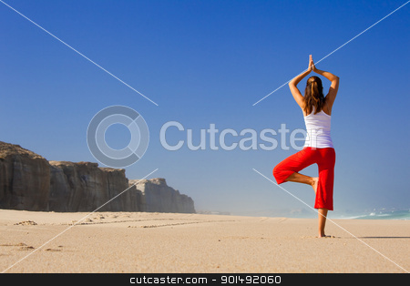 Young woman making Yoga stock photo, Beautiful young woman making Yoga exercises on the beach by ikostudio
