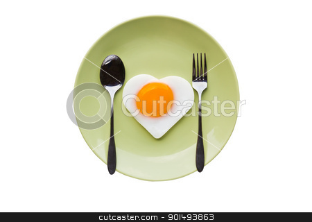 Fried egg heart and spoon stock photo, Fried egg heart and spoon on green dish by stoonn