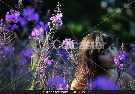 Woman Smelling Purple Flowers stock photo, Attractive brunette woman smelling purple flowers in a field, copyspace by Peter Veiler