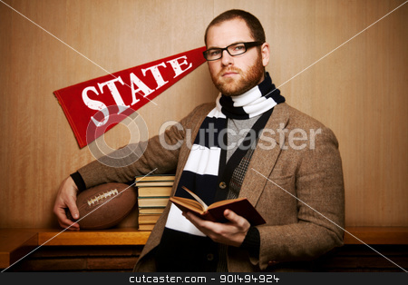 Young college man with books & ball stock photo, A young male college student set against a wood background holding his school textbooks and his football. by Kelli Harmon