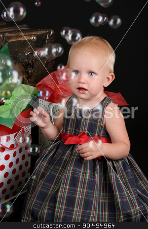 Christmas Bubbles stock photo, Cute blond toddler infront of an antique trunk with christmas presents by Vanessa Van Rensburg