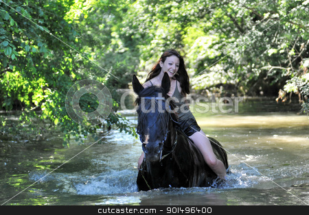 woman and  horse in the river stock photo, beautiful black horse in the sea and beautiful woman by Bonzami Emmanuelle