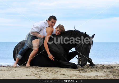 couple and  horse on the beach stock photo, beautiful black stallion laid down on the beach with young couple by Bonzami Emmanuelle