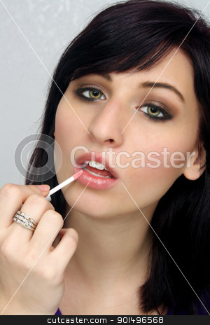 Beautiful Young Woman Applies Makeup (7) stock photo, A studio close-up of a lovely young woman with remarkable eyes, applying lip gloss or lipstick with a small applicator. by Carl Stewart