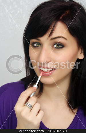 Beautiful Young Woman Applies Makeup (8) stock photo, A studio close-up of a lovely young woman with remarkable eyes, applying lip gloss or lipstick with a small applicator. by Carl Stewart