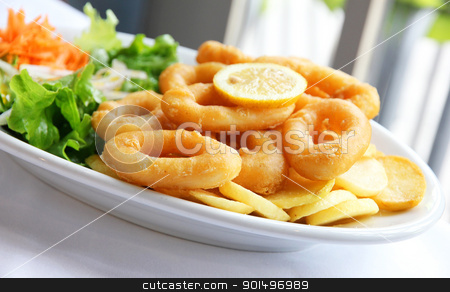 Deep batter fried squid rings calamari with green salad stock photo, Deep batter fried squid rings calamari with green salad on white plate  by Morozova Oxana