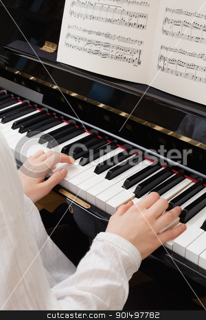 Playing the piano stock photo, Photo of a young girl playing the piano with sheet music open. by © Ron Sumners