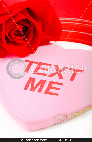 Valentines Day Message - Text Me! stock photo, A pink cookie and red rose use the tech-oriented phrase Text Me to send a flirtatious message to a loved one. by Karen Sarraga