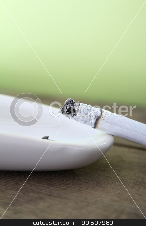 Cigarette stock photo, Burning cigarette resting on ashtray against green background by Vanessa Van Rensburg