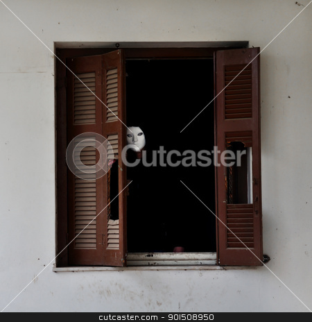 masked figure and broken window shutter stock photo, Man with white mask by the broken window shutter of an abandoned house. by sirylok