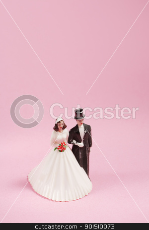 Old Cake Decoration stock photo, Vintage plastic wedding cake decoration on pink background. by Stocksnapper