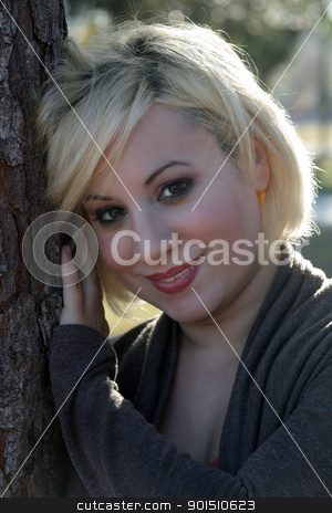 Beautiful Blonde Outdoors (3) stock photo, A close-up of a beautiful blonde with a captivating smile, leaning against a pine tree, backlit by the early-morning sun. by Carl Stewart